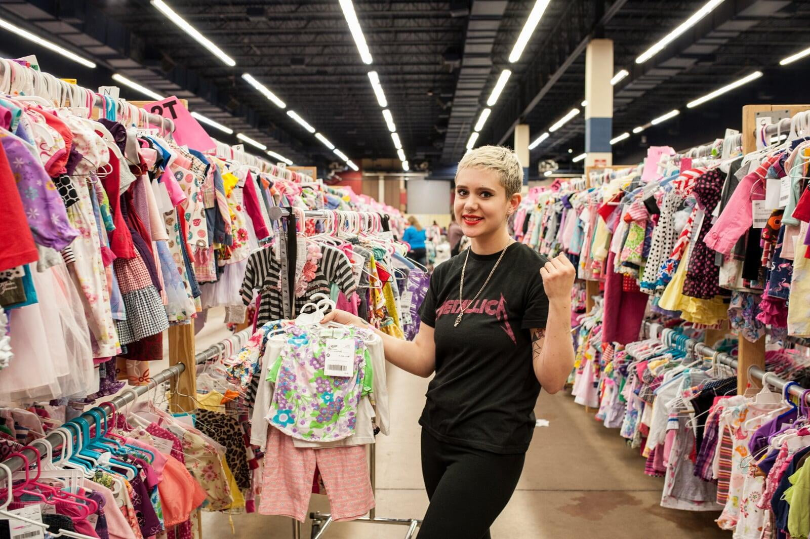 A young JBF shopper mom in a black Metallica T-shirt holds an outfit she intends to buy at her local JBF sale.