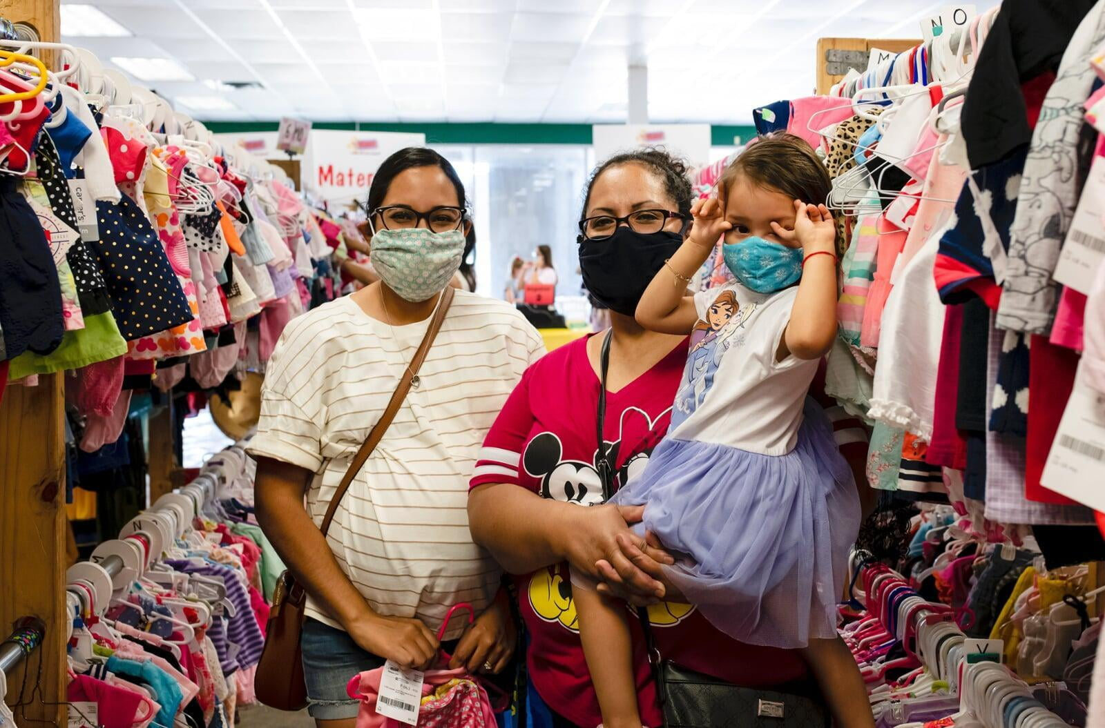 Two masked moms—one holding a child with a mask, the other pregnant—shop for their families at the local JBF sale.